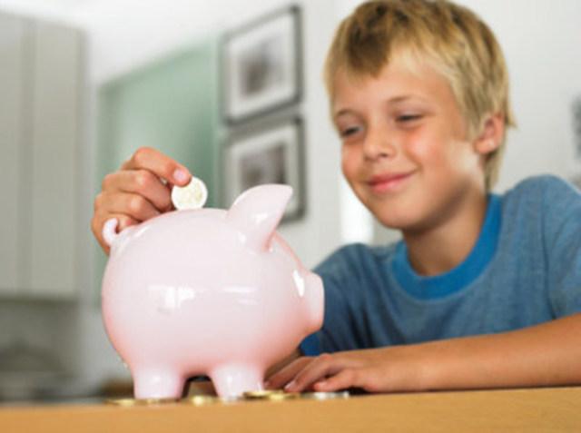 Boy (7-9) putting euro coin into piggy bank, smiling (CNW Group/Money Mentors)