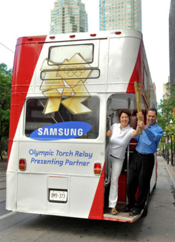 Jamie Piekarz, London 2012 Olympic Torchbearer, and Andrew Barrett, Vice President of Marketing, Samsung Electronics Canada, hop on a double-decker bus in Toronto for the unveiling of seven inspirational torchbearers chosen by Samsung Canada to participate in the London 2012 Olympic Torch Relay. (CNW Group/Samsung Electronics Canada)