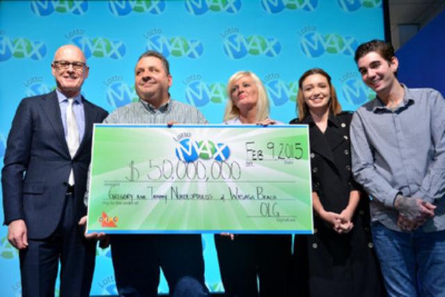 Greg McKenzie, vice-président principal, Loteries, remet le chèque de leur gain de 50 millions de dollars à LOTTO MAX à Gregory et Tammy Nikolopoulos, de Wasaga Beach, qui sont accompagnés de leurs enfants Caiden et Jennifer. (Groupe CNW/OLG Winners)