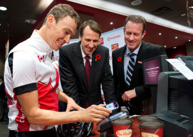 Simon Whitfield uses the CIBC Mobile Payment App to make the first SIM-based mobile payment in Canada, with David Robinson from Rogers, right and David Williamson from CIBC, centre. (CNW Group/CIBC)