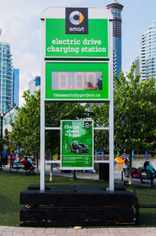 A sign emulating a traditional gas station price board can be seen at different locations throughout the city of Toronto this summer. smart representatives will be on site to encourage passersby to cast their vote for a future charging station location anywhere in Canada, and to provide information about the smart fortwo electric drive on display. (CNW Group/smart Canada)