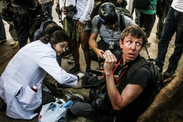 Canadian documentary filmmaker Jason O'Hara, who had been filming a demonstration in Rio de Janeiro before the 2014 World Cup final, receives emergency treatment after being beaten and kicked by police, who stole one of his cameras and broke another. O'Hara is the inaugural winner of the Portenier Human Rights Bursary for safety training from the Forum Freelance Fund. Photo credit: Bernardo Guerreiro/Midia Ninja Collective. (CNW Group/Canadian Journalism Forum on Violence and Trauma)