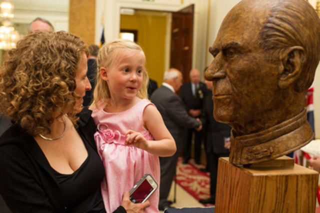 Canadian documentary photographer Scott McQuarrie captures exclusive images at private unveiling of a portrait sculpture of HRH, The Prince Philip, Duke of Edinburgh. Ceremony hosted by the RCR and His Excellency Gordon Campbell, Canadian High Commissioner. (l - r) Lisa McQuarrie and 4-year old Anna McQuarrie (CNW Group/MB Consulting)