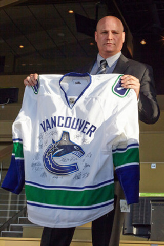 Ken Stratton, General Manager of Fraser Downs Racetrack and Casino holds an autographed Vancouver Canucks' jersey, a silent auction item that helped raise funds for the families impacted by the Langley barn fire.  (CNW Group/Fraser Downs Racetrack and Casino)