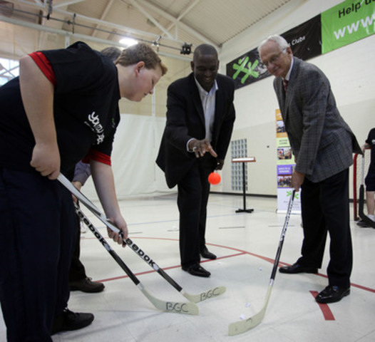 To celebrate a $100,000 grant from The Coca-Cola Foundation Rich Leslie, VP of Field Sales at Coca Cola Canada, gets the game started as a local member of The Boys and Girls Clubs of Hamilton faces off with Mayor Bob Bratina. (CNW Group/Boys and Girls Club of Hamilton)