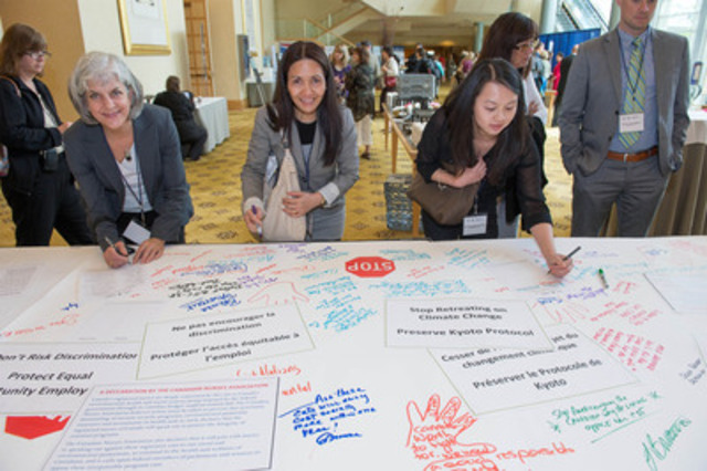 Registered nurses attending the Canadian Nurses Association's biennial convention add their names to a giant banner calling for the federal government to stop cuts to our nation's health, environment and social systems (CNW Group/CANADIAN NURSES ASSOCIATION)