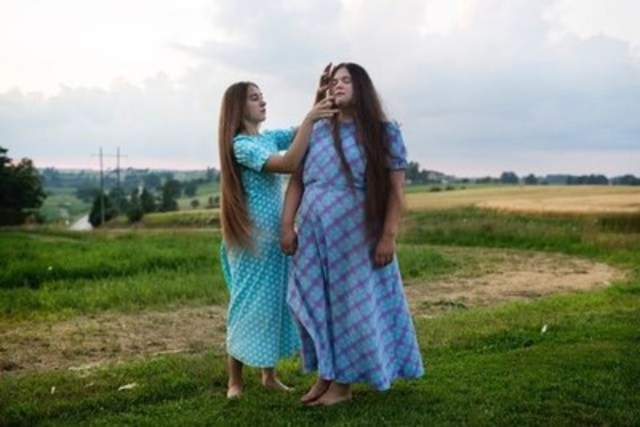 ANNIE SAKKAB / INDEPENDENT - FEATURE CATEGORY: Mennonite sisters Karli Martin, 16 (left) and Kayla Martin, 15 (right) enjoy having their hair down in the garden outside their home in Mapleton Township, Ontario July 15, 2015. Teenage girls within the conservative community start to wear their hair up with a prayer veiling or covering at the age of 15 and typically the next year or two they choose  between getting baptized and joining the church or leaving to pursue other lifestyle choices. Most women choose to stay and have a family. (CNW Group/News Photographers Association of Canada (NPAC))