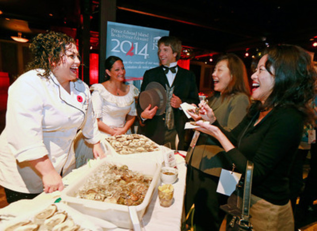"""Chef Ilona Daniel shucks and serves fresh Prince Edward Island oysters alongside the """"Father and Mother of Confederation"""" for tour operator JTB International representatives in Vancouver at the unveiling of the Official PEI 2014 Celebration Calendar. The province is inviting Canadians nationwide to be part of history by participating in these once-in-a-lifetime 2014 anniversary celebrations to commemorate the Charlottetown Conference - the event that led to the birth of Canada. (CNW Group/Prince Edward Island 2014 Inc.)"""