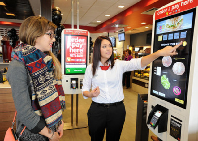 Rebecca Randall (L) orders a custom built Create Your Taste burger with Guest Experience Leader Erika Anderson at the Edmonton McDonald's restaurant on 199 St. and 62 Ave. NW on October 8, 2015. Edmonton is the first market in the country to roll out the new McDonald's Canada guest experience. (CNW Group/McDonald's Canada)