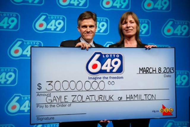 Rod Phillips, président et chef de la direction, Société des loteries et des jeux de l'Ontario, remet à Gayle Zolaturiuk, de Hamilton, le chèque du gros lot de 30 millions de dollars qu'elle a gagnés au tirage du 2 mars 2013 de LOTTO 6/49. (Photographe: Shan Qiao) (Groupe CNW/OLG Winners)