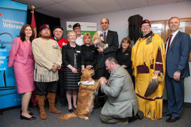 Veterans, representatives from St. John Ambulance, MP Royal Galipeau and therapy dogs Lucy and Tulip show their enthusiasm for the Minister of Veterans Affairs' funding announcement studying how dogs and horses can improve the overall mental health and well-being of Vétérans (CNW Group/Veterans Affairs Canada)