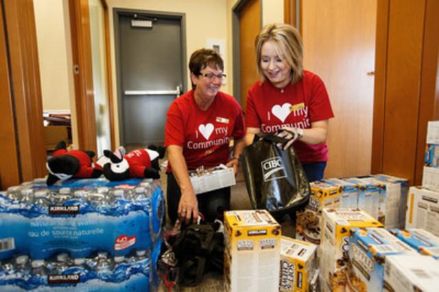 Cecily Clarke, directrice générale de la Banque CIBC (à gauche), et Gaye King préparent des trousses d'aide pour les clients au centre bancaire CIBC Fort McMurray, le vendredi 3 juin 2016. LA PRESSE CANADIENNE IMAGES/Codie McLachlan (Groupe CNW/Banque Canadienne Impériale de Commerce)