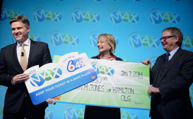 OLG's President and CEO Rod Phillips and OLG's Chair of the Board of Directors Philip Olsson present LOTTO MAX winner Kathryn Jones of Hamilton with an oversized, novelty magnet reminding her and all other lottery players to keep their tickets in a safe place. (CNW Group/OLG Winners)