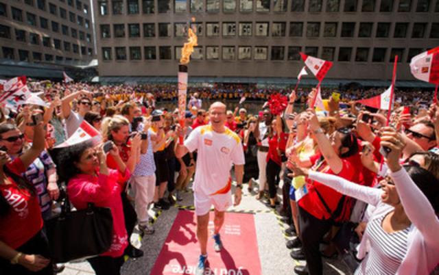 Victor Dodig, chef de la direction de la Banque CIBC, brandit la flamme des Jeux panaméricains de TORONTO 2015 lors d'une célébration pour les employés dans le centre-ville de Toronto (Groupe CNW/Banque Canadienne Impériale de Commerce)