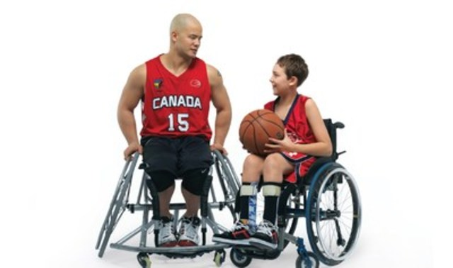 Le double médaillé d'or paralympique en basketball en fauteuil roulant David Eng avec un jeune athlete. (Groupe CNW/Comité paralympique canadien (CPC))