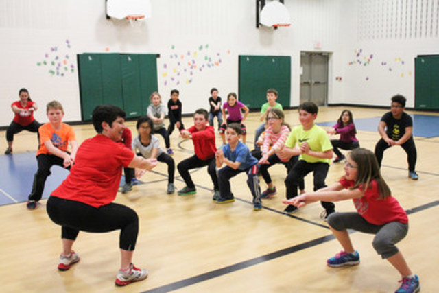 GoodLife4Kids Coach Jennifer Zammit demonstrates proper squat form with a group of grade four students. (CNW ...