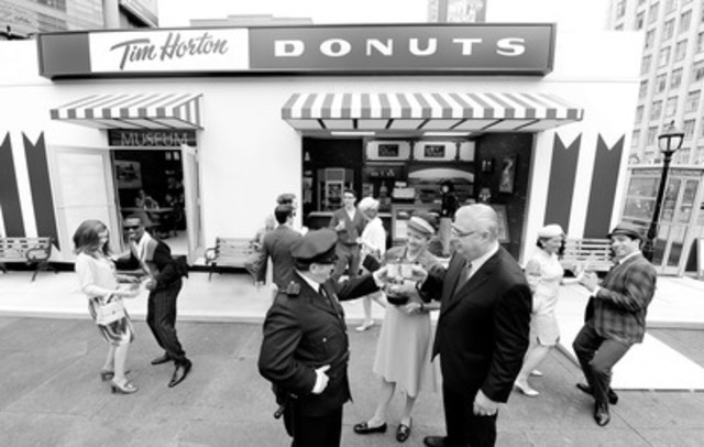 Marc Caira, President & CEO, Tim Hortons Inc., celebrates the company's 50th anniversary by turning back the clock at Toronto's Yonge-Dundas Square. The bustling corner was transformed into a scene from the 1960s with a replica of Tim Hortons first restaurant from 1964. #Tims50th (CNW Group/Tim Hortons)
