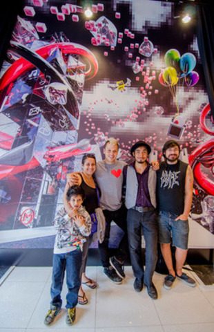 Creator of the Lovebot and Love Invasion Matthew Del Degan poses with young artists from Toronto-based community arts enterprise SKETCH in front of the mural they created for Virgin Mobile's new Queen Street West store. (CNW Group/Virgin Mobile Canada)