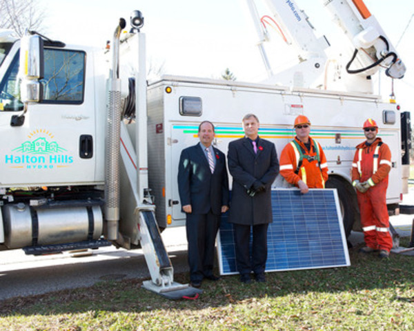 From left, Halton Hills Mayor Rick Bonnette and Halton Hills Hydro President and CEO Art Skidmore join power line technicians Hessel Faber and Matt Stephens before technicians mount a unique solar-smart grid panel on Trafalgar Road in Ballinafad. (CNW Group/Halton Hills Hydro)