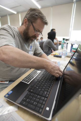 Siemens Canada employee Luc Portelance affixes Arabic language stickers to a keyboard at a workshop preparing computers for donation to Syrian refugees in Calgary (CNW Group/Siemens Canada Limited)