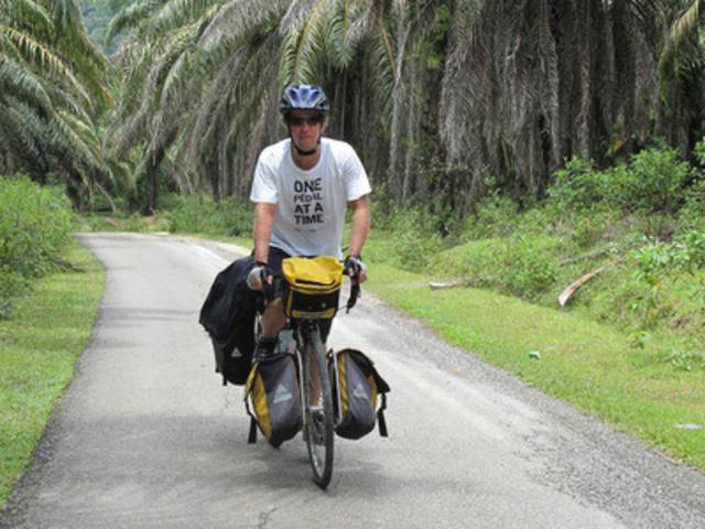 """Mental health advocate Michael Schratter cycling through the jungles of Malaysia in March 2011 on his """"Ride Don't Hide"""" journey. (CNW Group/Canadian Mental Health Association, BC Division)"""