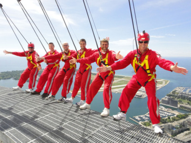 Sportsnet's Buck Martinez (far left) and Pat Tabler (far right) hover 1,168 feet over Toronto during the CN Tower EdgeWalk earlier today, to raise funds for Jays Care Foundation. Also pictured are the top four donors from the campaign. (CNW Group/Sportsnet)