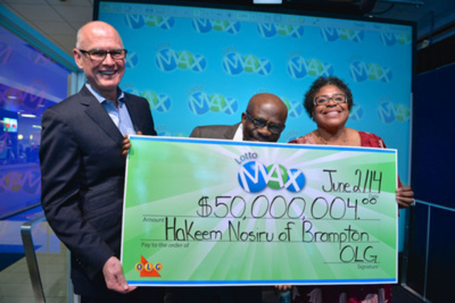 OLG's Senior Vice President of Lottery Greg McKenzie presents Brampton resident Hakeem Nosiru and his wife Abiola with a cheque for $50,000,004 at the OLG Prize Centre Monday. Hakeem, who won the January 17, 2014 LOTTO MAX jackpot, gave the cheque a celebratory kiss just as he always does when purchasing his lottery tickets. (CNW Group/OLG Winners)