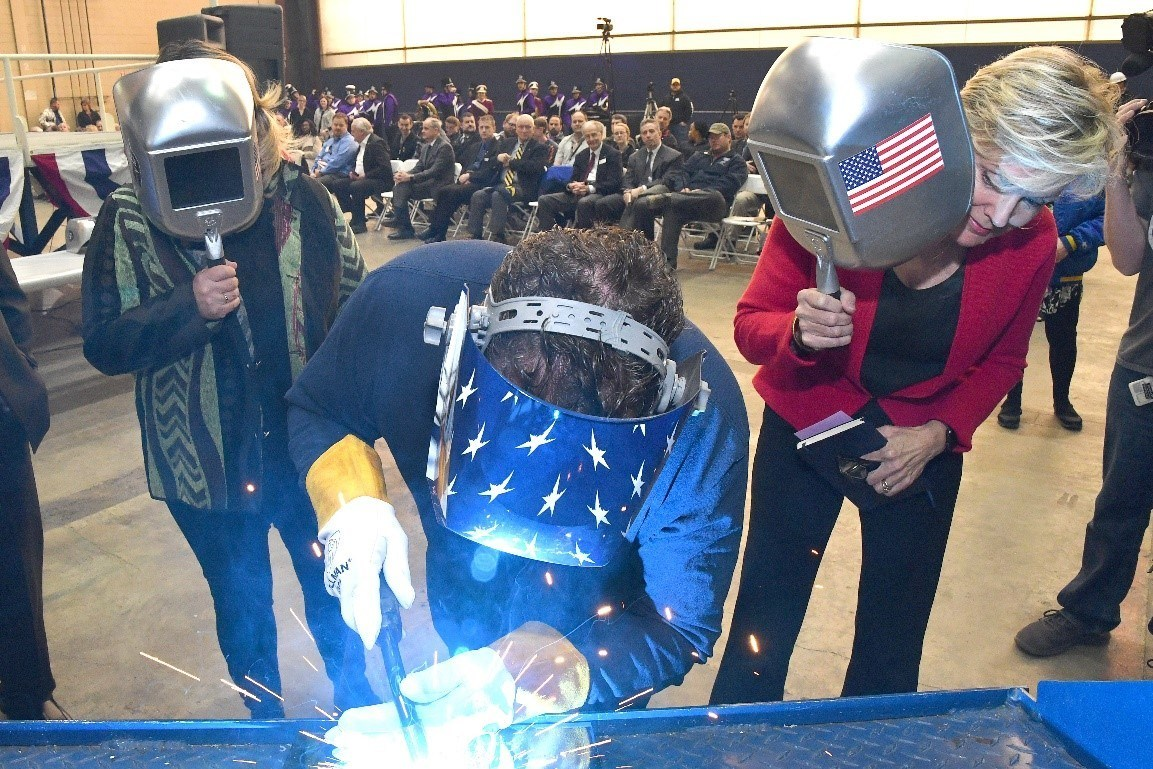 A welder authenticates the keel of LCS 25, the future USS Marinette, by welding the initials of ship sponsor Jennifer Granholm. Lockheed Martin Photo.