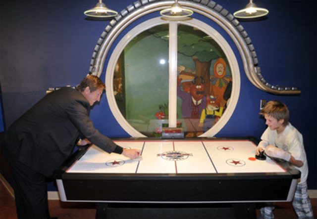 Nine-year-old patient Connor Kozack, goes for a goal on the Great One, Wayne Gretzky, during a celebration event at SickKids marking TD's $15 million donation milestone, in Toronto, November 9, 2011. (CNW Group/SickKids Foundation)