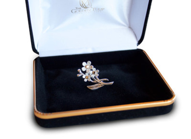 This custom designed, sterling silver pin features three forget-me-not blossoms with an inset of certified Anaconda Newfoundland Gold representing the past, present and future of the Royal Newfoundland Regiment. (CNW Group/Anaconda Mining Inc.)