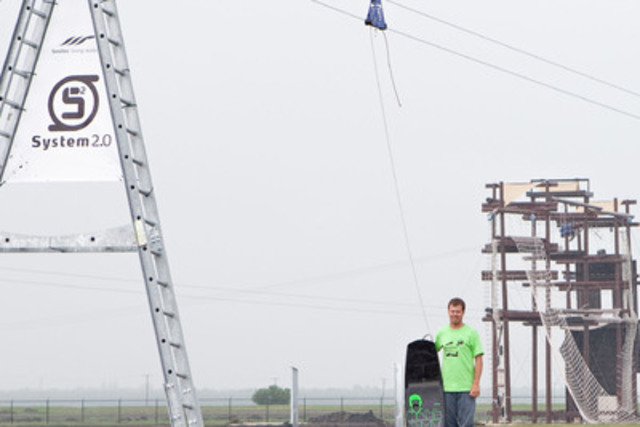 Owner Jason Rohs stands next to a cable wakeboarding tower with the high-ropes course in the background. (CNW Group/Adrenaline Adventures)