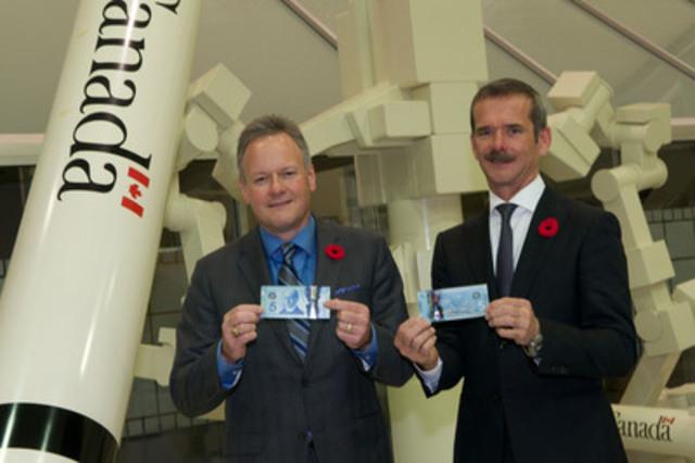 M. Stephen S. Poloz et M. Chris Hadfield devant une réplique grandeur nature du Canadarm2 et de Dextre au lancement officiel de la nouvelle coupure de 5 dollars en polymère, qui s'est déroulé à l'Agence spatiale canadienne, à Saint-Hubert (Québec). (Groupe CNW/Banque du Canada)