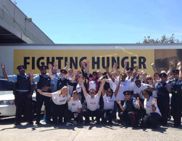 """Michael """"Pinball"""" Clemons Foundation, Toronto Police and Purolator tackling hunger as part of the JUST GIVE Five Days of Giving Cram-a-Cruiser Challenge on June 3. (CNW Group/Michael """"Pinball"""" Clemons Foundation)"""