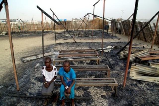 À droite, Chubat, âgée de 12 ans, est assise avec son amie dans les ruines calcinées de son école au Soudan du Sud. L'école primaire soutenue par l'UNICEF a été incendiée lors des combats qui ont fait rage les 17 et 18 février 2016, et qui ont causé la mort d'au moins 18 personnes. © UNICEF/UN018992/George (Groupe CNW/UNICEF Canada)