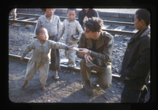 This photo from 1953 shows a Canadian gunner handing candy to a Korean boy at the rail yards in Tokchon, South Korea. (CNW Group/Canadian War Museum)