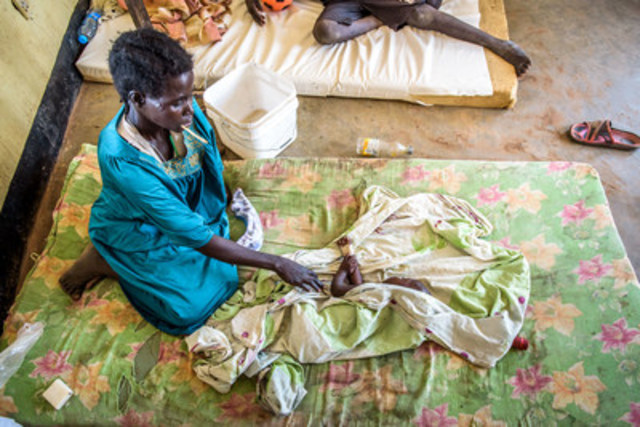 Adut Atway, 28, sits next to her ill one year-old baby, Makuei Guanat, who sleeps on a mattress at Warrap State Hospital because there are not enough beds. (CNW Group/World Vision Canada)