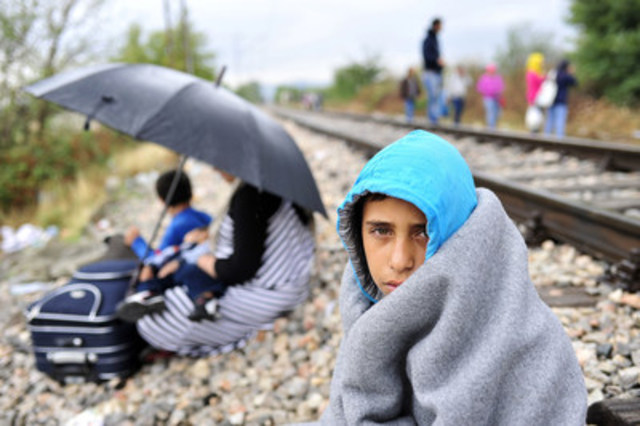 A boy sits beside a railroad track on a rainy day near the town of Gevgelija, in the former Yugoslav Republic of Macedonia, near the Greek border. Next to him, a woman and a young child sit with their luggage beneath an umbrella. Behind them, others who have fled their homes amid the ongoing refugee and migrant crisis walk beside the railroad track. (CNW Group/UNICEF Canada)
