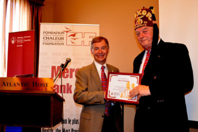 Shriners Winston MacKay and Daryll Stothart from the Luxor Temple in New Brunswick were recognized for their leadership in the development of the Bathurst Outreach Clinic over the past 10 years. In the photo, François Fassier, M.D., Emeritus Chief of Staff at Shriners Hospitals for Children-Canada presents Daryll Stothart with a special recognition certificate (CNW Group/SHRINERS HOSPITAL FOR CHILDREN (CANADA))
