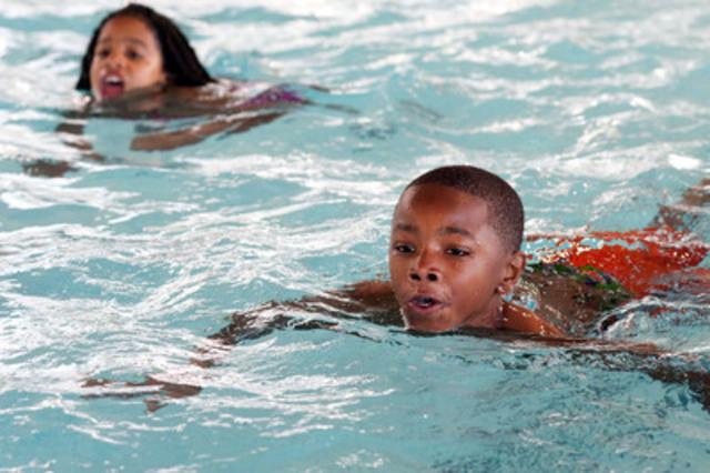 Jusiah Hussey (au premier plan) et Elizabeth Ackah (en arrière-plan) de l'École publique Nelson Mandela Park apprennent des techniques de sécurité aquatique à l'occasion du 10e anniversaire du programme « Nager pour survivre » au Centre aquatique Regent Park, à Toronto, le 4 juin.  (Groupe CNW/Société de sauvetage)
