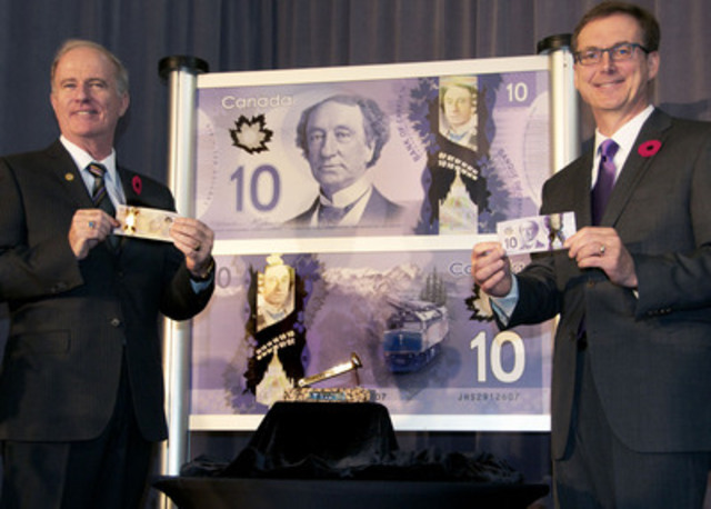 Marc Laliberté and Tiff Macklem pose with the last spike intended to mark the completion of the railway nearly 130 years ago. The photo was taken during an official ceremony to issue the new $10 polymer bank note into circulation, at the Pacific Central Station in Vancouver, British Columbia. (CNW Group/Bank of Canada)