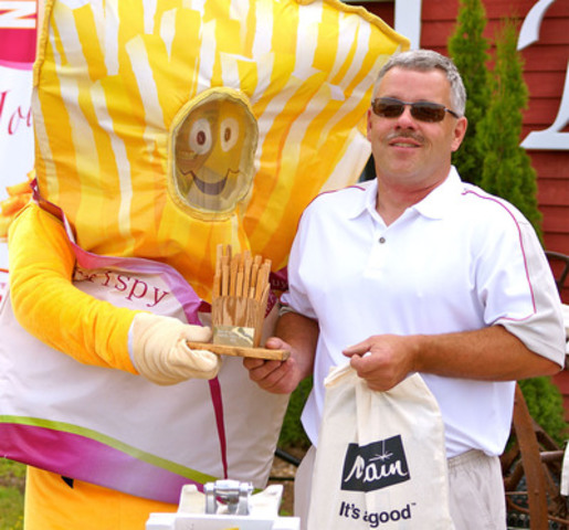 Peter Tweedie of Lakeside Farms was crowned the fastest French fry cutting champ at today's National French Fry Day celebrations in Florenceville-Bristol, NB for cutting 15.08 kg of fries in three minutes. The town's mascot, Crispy, presented the coveted trophy and McCain prize pack at Potato World. (CNW Group/Town of Florenceville-Bristol)