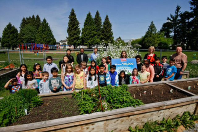 Alderson Elementary School staff and students, along with representatives from Staples Canada, celebrate having won a computer lab worth $25,000 in the Staples Canada Recycle for Education Computer Lab Contest in front of their school garden. (CNW Group/Staples Canada Inc.)