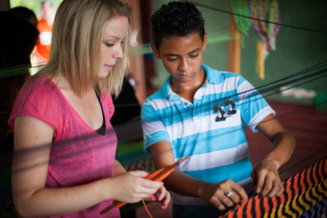 Lyndsay Morrison of CTV Kitchener with Ellison (14), participating in a World Vision after school program where he learns to make hammocks. Each hammock will sell in the market for $40 CDN. (CNW Group/World Vision Canada)