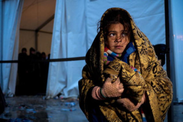 A girl covered in a heavy blanket stands outside a tent at the Vinojug reception centre for refugees and migrants in the former Yugoslav Republic of Macedonia. Heavy rain and near freezing conditions are challenging the refugees and aid organizations providing them with warm winter clothing and supplies. ©UNICEF/UN03023/Gilbertson VII Photo (CNW Group/UNICEF Canada)