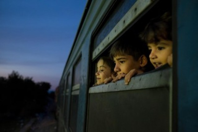 In October 2015 in the former Yugoslav Republic of Macedonia, three children look out of a train as refugees, mostly from Syria, Afghanistan and Iraq, board the train at a reception center for refugees and migrants in Gevgelija. (CNW Group/UNICEF Canada)