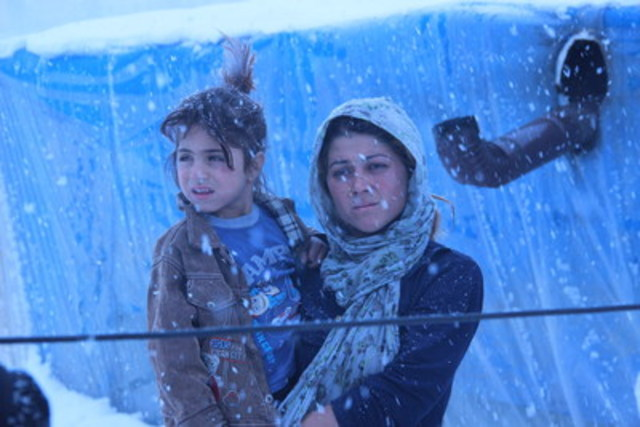 A woman carrying a girl wearing a light jacket stands outdoors in heavily falling snow, near a tent shelter, on a bitterly cold day in a host community in Dikmen Valley – an urban transformation project area – in Ankara, the capital. A pipe behind them provides heat in the tent. Heavy snowfall, snow storms and strong winds are making daily life harder, especially for children who lack winter clothing. (Photo credit: © UNICEF/UNI177414/Yurtsever) (CNW Group/UNICEF Canada)