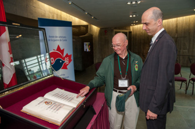 Veteran Doug Steer points out to Minister Blaney the name of his brother in the Korean War Book of Remembrance displayed at the Canadian War Museum (CNW Group/Veterans Affairs Canada)