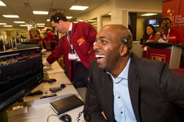 NBA legend John Salley makes a trade on CIBC Miracle Day in Toronto, where celebrities and clients come together to help raise millions for kids. This was the 31st anniversary of the event, which has raised nearly $80 million in Canada for children's charities. (CNW Group/CIBC)