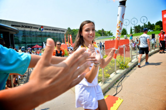 Ontario Science Centre-nominated torchbearer Marissa Papaconstantinou is all smiles as she high-fives visitors while carrying the Pan Am flame at the Centre on Monday, July 6 as part of the TORONTO 2015 Pan Am Games Torch Relay. The Centre held a free community torch relay celebration that included sports-related programming, sponsor activations and live music.1 (CNW Group/Ontario Science Centre)
