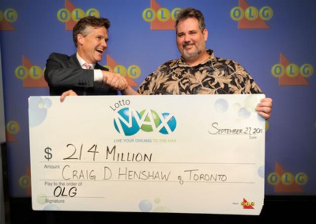 President and CEO of OLG Rod Phillips, left, presents GTA area school teacher Craig Henshaw with a cheque for $21.4 million at the OLG Prize Centre Tuesday afternoon. Henshaw won the LOTTO MAX jackpot prize after purchasing a ticket for the July 8th draw. (CNW Group/OLG Winners)